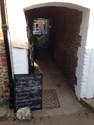 View through a narrow stone archway, down a lane. Book sale at the bottom of the lane. Signs in the foreground advertise used book sale and homemade jam for sale.
